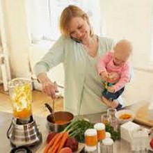 Mãe com bebê ao colo na cozinha