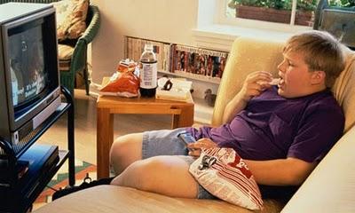 criança a comer em frente da tv